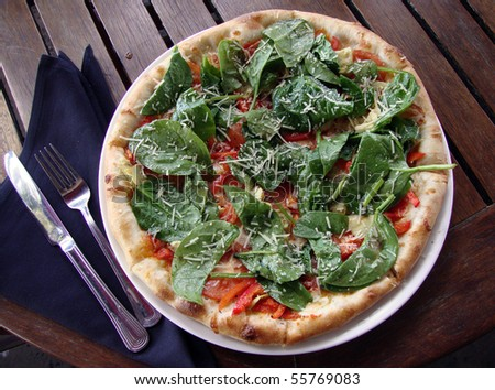 Spinach Margarita Pizza with a fork and knife on top of a napkin on an outdoor table.
