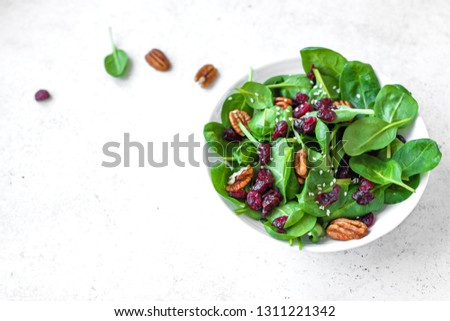 Spinach salad with  pecan nuts and dry cranberries on white background, copy space. Heathy clean vegan raw food, fresh salad.