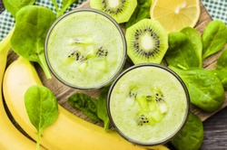 Spinach smoothie. Fruit green smoothies in glass and ingredients. Spinach, banana, kiwi, lemon. Detox, diet, healthy, natural, organic food. Vitamin charge. Top view