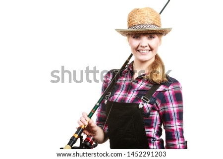 Spinning, angling, cheerful fisherwoman concept. Happy woman in sun hat holding fishing rod, having fun and smiling.