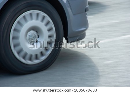 Spinning back wheel of car on uk road.Moto abstract,theme.Panning shot,movement,motion,dynamics.Cold blue tones.,space for edit. #1085879630