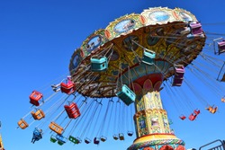 Spinning carousel ride with swings at amusement park.