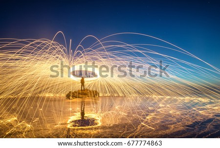 Stock Photo Spinning fire sparks of the steel wool by the sea in night with reflection, Isla Vista, Santa Barbara, California, United State.