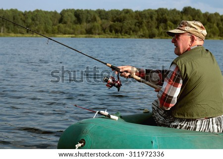 Spinning fisherman on a boat fishing #311972336