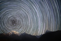 Spinning Universe. Star trails over the mountains. Annapurna South (7,219 m), Hiunchuli (6,441 m),  Gangapurna (7,454 m) and Annapurna III (7.555 m), and unclimbed mountain Machhapuchhre (6,997 m).