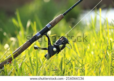 spinning with reel on the background of green grass #216066136