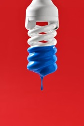 Spiral fluorescent bulb with blue paint on the red background in the studio. Paint is dripping down from it. Closeup. Vertical.