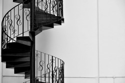 Spiral iron staircase with strong detail isolated against white wall in monochrome with space for copy design