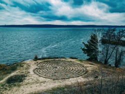 Spiral labyrinth made of stones on the coast, aerial view