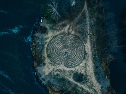 Spiral labyrinth made of stones on the coast, top view from drone