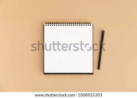 Spiral notebook page, list and a pen on a beige background. Flat lay.