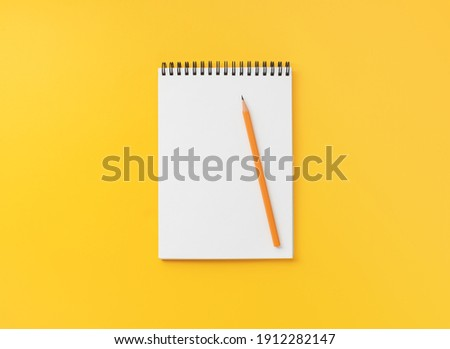 Spiral notebook with pencil on yellow table, top view, flat lay   Сток-фото ©