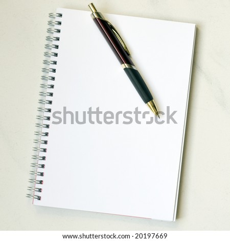 Spiral notepad with pen on marbled desk