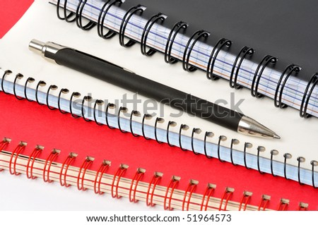 Spiral notepads and ball pen on white background
