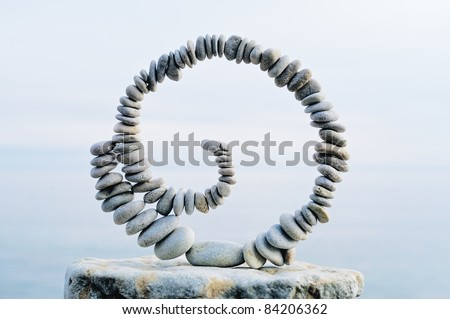 Spiral of pebbles on the top of boulder at the sea