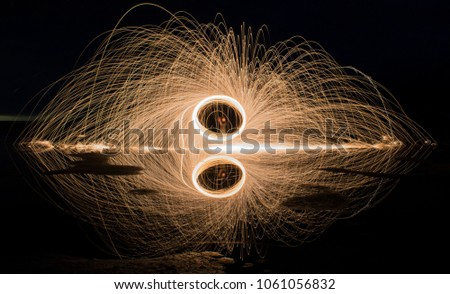 Spiral of sparks being thrown out in all directions capture with a long exposure. Added with the reflection of the water. Leaving you with a exciting but at the same time calming piece of art.