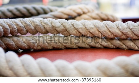 Spiral rope resting on a red boat deck. Very shallow depth of field