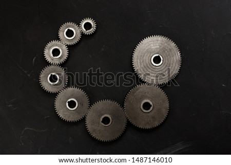 Spiral set of variety cogwheels on the black background. Steampunk style layout. Spiral sequence concept. Flat lay, top view.