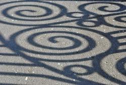 Spiral shadows on asphalt path; abstract background.