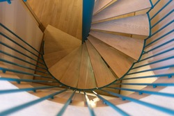 Spiral staircase, forged green handrail and wooden steps in modern home. Horizontally framed shot.