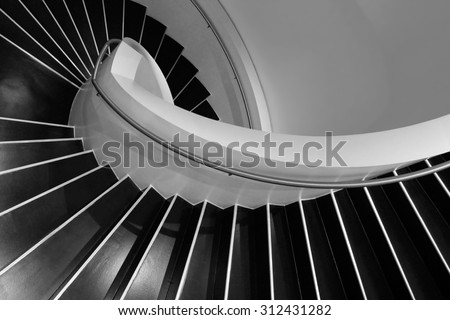 Spiral staircase in a contemporary building with interiors designed in style of minimalism. Sample image of modern architecture with distinguishing shades of black and white.