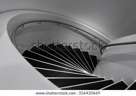 Spiral staircase in minimalism style. Black and white photo of contemporary architecture / modern interior design with soft shades of gray.