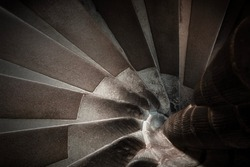 Spiral staircase vanishing downstairs in brown tones.Top-down view of an old winding staircase with stone steps. Stone steps stairs of old building. Background with construction of curving shape