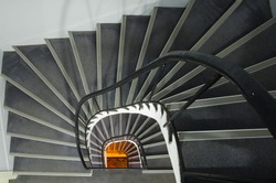 Spiral staircase with warm orange light at the end