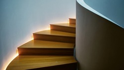 Spiral steps made of light wood illuminated on one side.