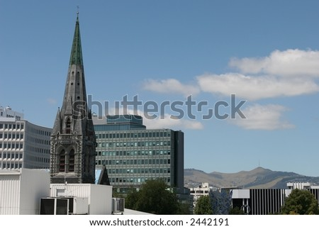 Spire of Christchurch Cathedral, jutting out of the cityscape.  Port hills in the background.