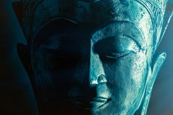 Spiriitual enlightenment. Enlightened buddha face statue close-up. Bold graphic image with atmosperic blue tone light and star highlight. Religious lifestyle awakening via meditation. Serene power.