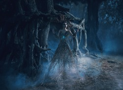 spirit wanders  woods in dark magic forest. Elf girl tree took root near mighty oak, mystical image, spells, fashion design creative color toning. Soul magician witch. Smoke nigth fog. Art photography