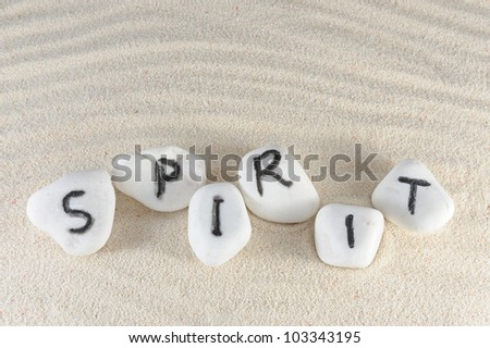 Spirit word on group of stones with sand background