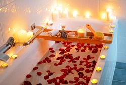 Spiritual aura cleansing flower bath for full moon ritual with candles, aroma salt, lavender and rose petals.