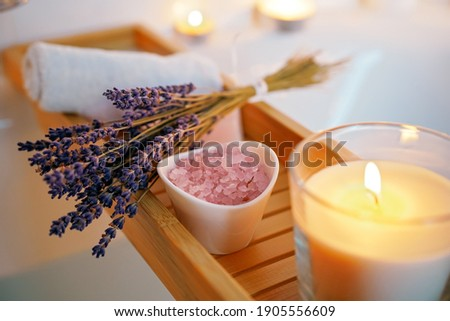 Spiritual aura cleansing ritual bath for full moon ritual. Candles, aroma salt and lavender on tub table, close up Photo stock ©