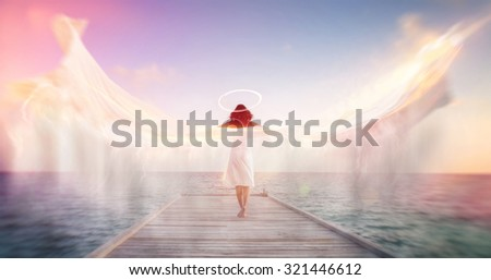 Stock Photo Spiritual conceptual image of a female angel standing barefoot on an ocean jetty in a white dress with a halo and outspread wings showing motion blur with ethereal colorful sun flare effects