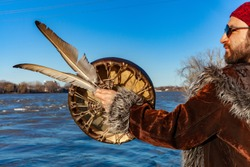 Spiritual man worships natural river. A close-up view of a sacred drum and symbolic eagle feathers in the hand of a young Caucasian guy, standing on a riverbank beneath a clear blue sky.