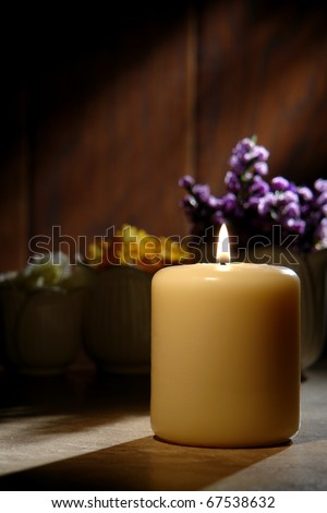 Spiritual reflection pillar candle burning with a soft glowing flame and flowers in vases in a peaceful religious setting for meditation and contemplation