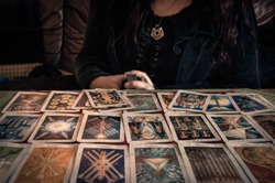 Spiritual wicca witch reading occult mystic old tarot cards on table for a magical pagan ritual psychic destiny reading - Concept of supernatural, witchcraft, destiny and mystical fortune-telling.