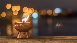 Spirituality, soul abstract, death, and world human spirit day concept with light candle and hot fire burning brightly in blur dark black waterfront riverfront reflective wavy ripple tide