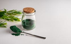 Spirulina Chlorella algae powder in a glass jar and in a spoon on a white background. Horizontal orientation. Scientists are developing research on algae. Bio-energy, biofuel, energy research