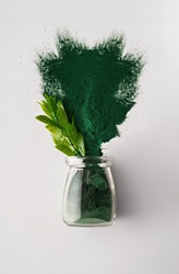 Spirulina Chlorella algae powder in a glass jar and in a spoon on a white background. Vertical orientation. Scientists are developing research on algae. Bio-energy, biofuel, energy research