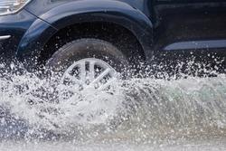 Splash by a car as it goes through flood water