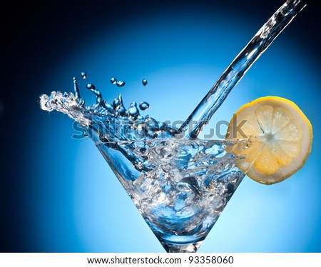 Splash from pouring martini into the glass. Object on a blue background.