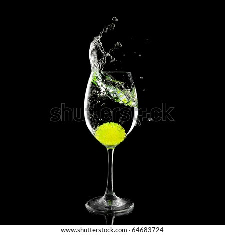 splash in a glass with lemon ball and ice on a black background
