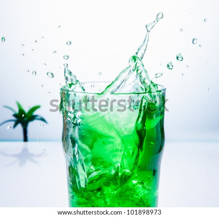 Splash of a green cocktail on a white background with a palm