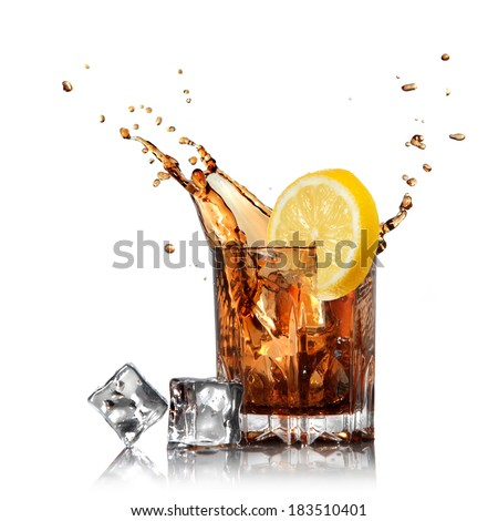 splash of cola in glass with lemon and ice isolated on white