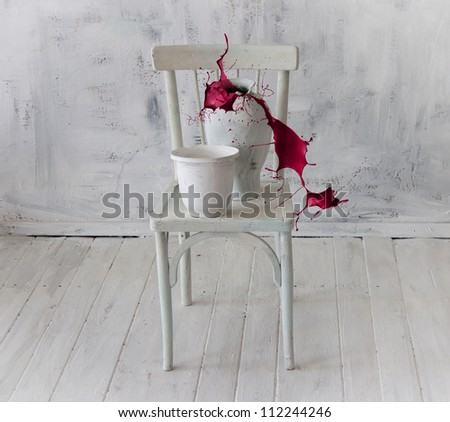 Splash of red paint from a pitcher standing on a white chair. Abstract composition of white objects in a white interior.