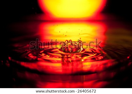 Splash of water drop in red-yellow palette on black background