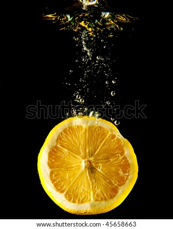 Splash water with lemon over black background